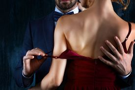 Elegant Couple In Love. Rich Tidy Neat Man Male Hugs Luxury Woman Female In Red Evening Dress With E