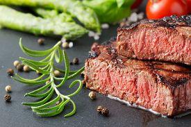 Grilled And Sliced Steak On Slate Background