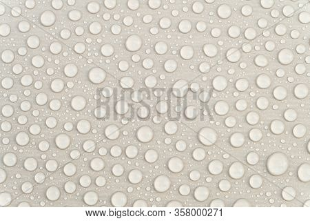 Fresh Water Drops On A Gray Glossy Surface Close-up. Waterproofing Stain Dye Coating For Constructio