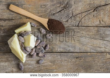 Cocoa Butter Or Cocoa Bean Solid Oil With Cacao Powder In Spoon Or Bowl And Raw Cocoa Beans On Rusti