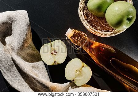 Still Life With Apples And A Bottle Of Apple Cider Or Juice, Or Vinegar On A Dark Background. The Co