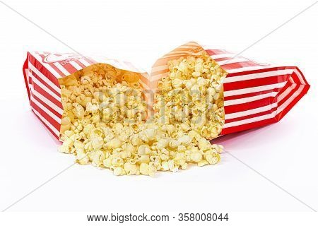 Horizontal Shot Of Two Bags Of Popcorn Laying Toward Each Other Spilling The Popcorn In Both.  White