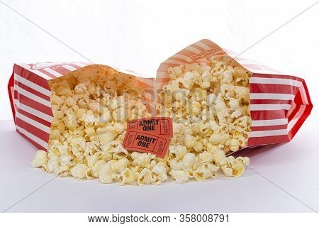 Horizontal Shot Of Two Bags Of Popcorn Laying Toward Each Other Spilling The Popcorn In Both With Tw