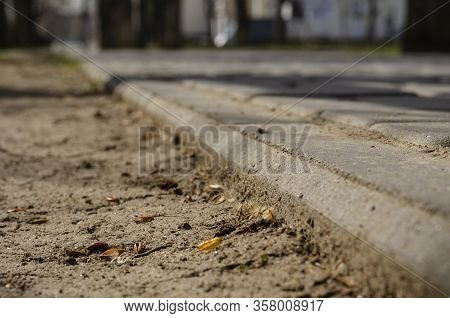 The Outer Edge Of The Sidewalk Close-up. Bright Spring Sun In A Big City. Walk Along The Spring Stre