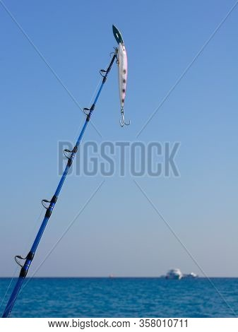 Saltwater Fishing - Fishing Rod (spinning Rod) With Wobbler On Blue Background