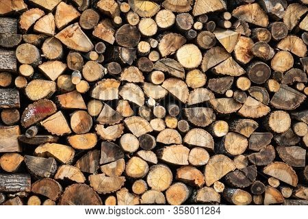 Firewood storage concept. Natural sawn wood stacked in row, texture. Stacks of chopped logs as background. Romantic winter in front of fireplace. Wallpaper.