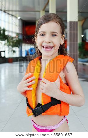 Little sorrowful girl wearing orange life-jacket laughs after swimming in pool.