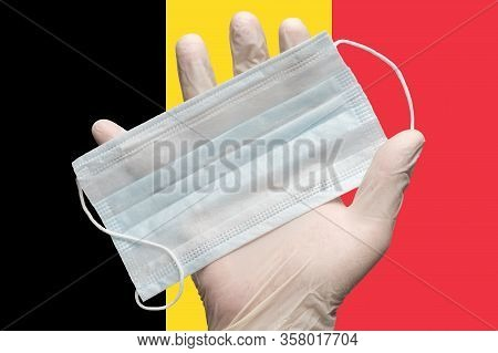 Doctor Holds Face Mask In Hand In White Medical Gloves On Background Colors Flag Of Belgium. Concept