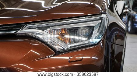 Front View Of A Modern Luxury Car. Futuristic Design Of Headlights And Front Of The Car. Car Service