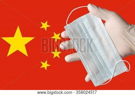 Doctor Holds Medical Face Mask In Hand In White Gloves On Background Colors Flag Of China. Concept P