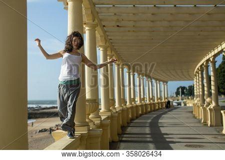 Beautiful asian woman walks along the railing of the sea promenade.