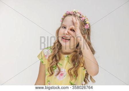 Portrait Of Surprised Teenager Girl Making Ok Hand Gesture With Eyes Looking Through Fingers Isolate
