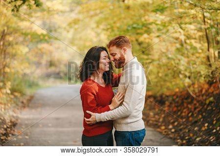 Portrait Of Beautiful Couple Man Woman In Love. Boyfriend And Girlfriend Hugging Outdoor In Park Roa