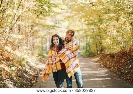 Beautiful Couple Man Woman In Love. Boyfriend And Girlfriend Wrapped In Yellow Blanket Plaid Hugging