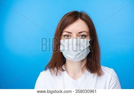 Brunette Woman Wearing Aseptic Mask. Light Blue Background