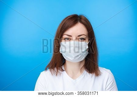 Woman In Aseptic Mask. Light Blue Background