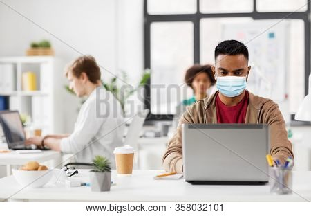 business and creative people concept - young indian man with laptop computer wearing protective medical mask for protection from virus disease working at office