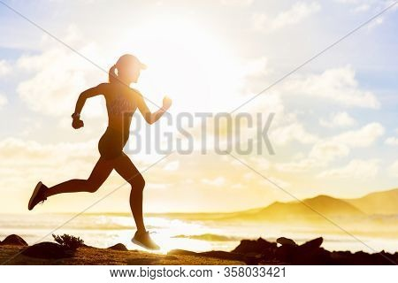 Summer workout athlete runner girl trail running on summer beach. Fit body silhouette of sports Woman in sportswear cap sprinting motion in outdoors nature training cardio with jogging exercise.