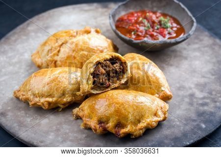 Traditional South American empanada de carne offered with a chili dip as closeup on a rustic modern design plate
