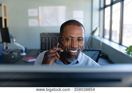 Front view of an African American businessman working in the modern office, sitting by a desk, smiling, talking on his smartphone and using a desktop computer. Social distancing and self isolation in