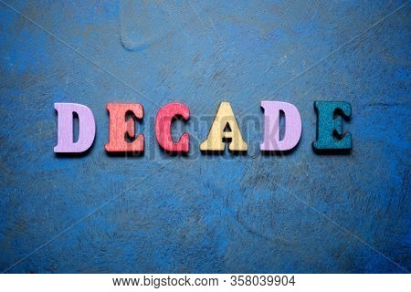 Decade word on a blue table.