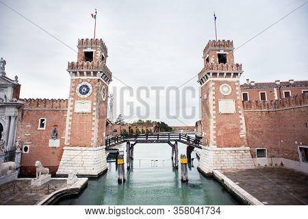 Venice. Italy - May 13, 2019: The Main Gate at the Venetian Arsenal (Arsenale di Venezia). View from Ponte del Paradiso. Canal Rio dell Arsenale.