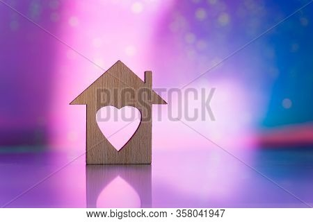 Wooden Icon Of House With Hole In The Form Of Heart On Pink And Purple Blurred Galactic Background W