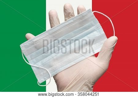 Doctor Holds Medical Face Mask In Hand In White Gloves On Background Colors Flag Of Italy Or Italian