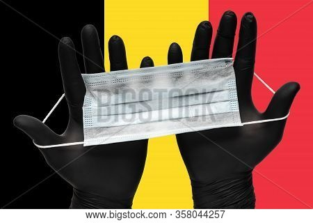 Doctor Holds Medical Face Mask In Hands In Black Gloves On Background Colors Flag Of Belgium. Concep