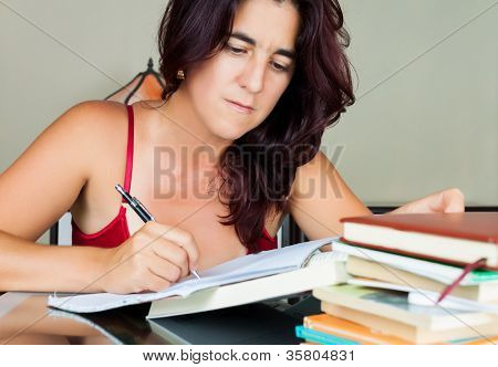 Beautiful adult hispanic woman writing or studying  with a stack of books on her desk