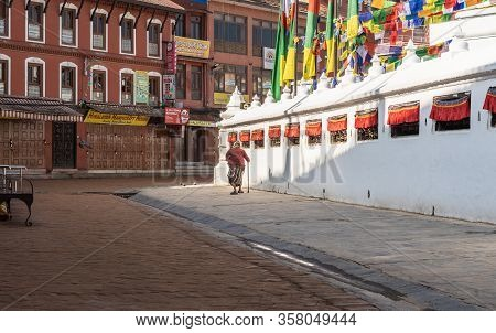 March 25, 2020. Kathmandu, Nepal. The ​​stupa Bouda Closed On Quarantin. A Lonely Grandmother Makes