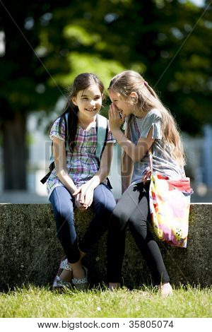 Two little girls whispering secrets while sitting outdoors