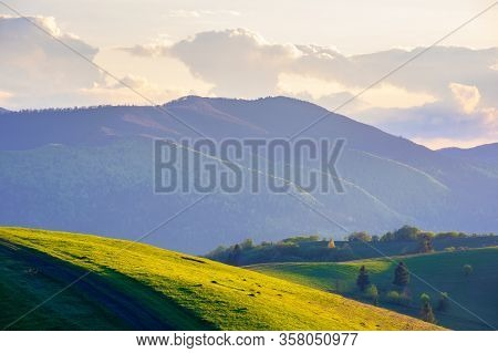 Mountainous Countryside In Springtime At Dusk. Path Through Rolling Hills. Ridge In The Distance. Cl