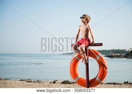 One Little Kid In Red Shorts And Sunglasses Sitting On Beach With Lifebuoy During Tan Sunbathe Leisu