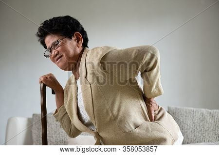 Asian Old Woman Sitting On Sofa And Having A Back Pain, Backache At Home. Senior Healthcare Concept.