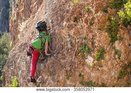 The Child In Helmet Is Climbing On A Natural Terrain. A Boy Climbs A Rock On A Background Of Mountai