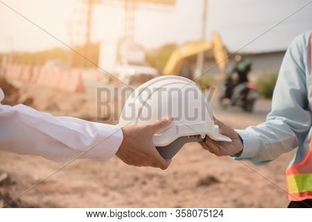 Foreman Giving Hard Hat To Partner For Use Hard Hat To Protect In Building Construction Site