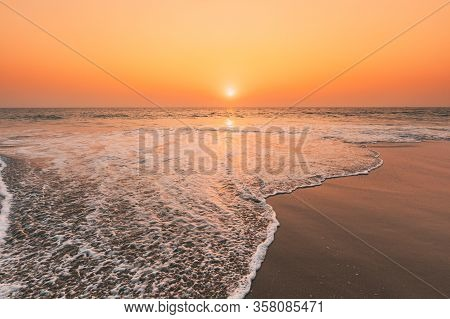 Sunset Sun Above Sea. Natural Sunrise Sky Warm Colors Over Ripple Sea. Ocean Water Foam Washing Sand