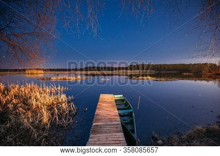 Belarus, Eastern Europe. Real Night Sky Stars Above Old Pier With Moored Wooden Fishing Boat. Natura