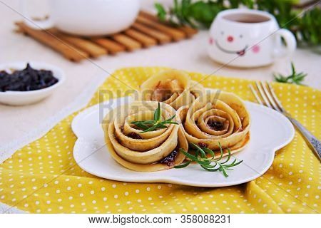 Pancakes, Rolled Up In The Shape Of A Rose Flower, On A White Plate On A Light Concrete Background.