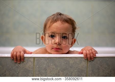 A Cute Caucasian Baby Peeks Out Of The Bathtub, Put Hands On The Side Of The Bath And Looks To The C