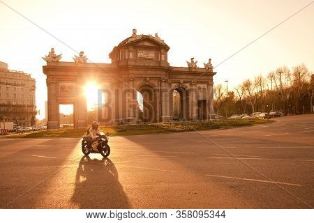 Madrid, Spain - April 05, 2010: Motorcyclist Passing By In Front Of Sunlight At Puerta De Alcala In