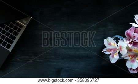 Flat Lay Home Office Desk. Working At Home Women Workspace With Laptop, Flowers Bouquet On A Dark Br