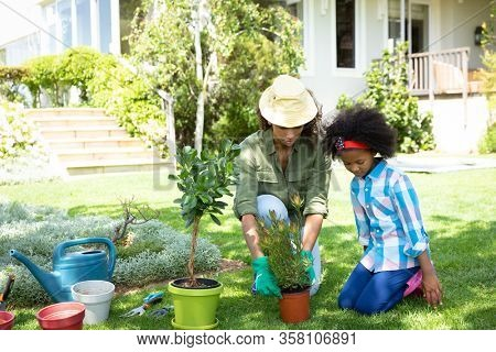 Front view of an African American woman and her daugther in the garden, kneeling and potting a plant together. Family enjoying time at home, lifestyle concept