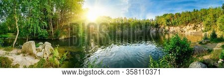 Panoramic Landscape Shot Of Idyllic Lake Surrounded By Trees And Cliffs, With The Sun Glowing On The