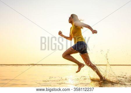 ฺbarefoot Woman Running Jogging In The Shallow Water On Beach In Sunlight Of Morning. There Are Drop
