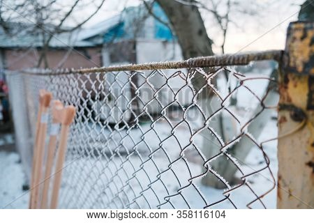 A Fence Which Has Become Rusted Through Years Of Neglect. Crutches On The Background