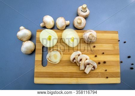 Three Sliced Champignons On A Wooden Board Onion Rings And White Champignons On A Gray Background