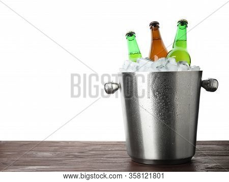 Metal Bucket With Bottles Of Beer And Ice Cubes On Wooden Table Against White Background. Space For