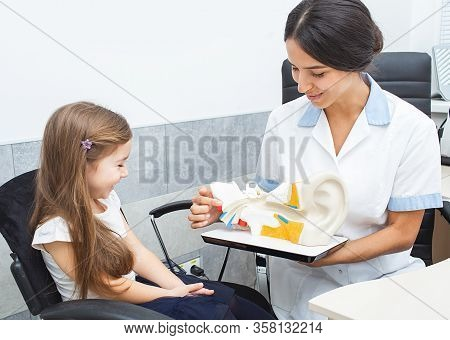 Audiologist Showing A Little Girl An Eardrum On Model Of Human Ear. Complaints Of Bed Hearing In Chi